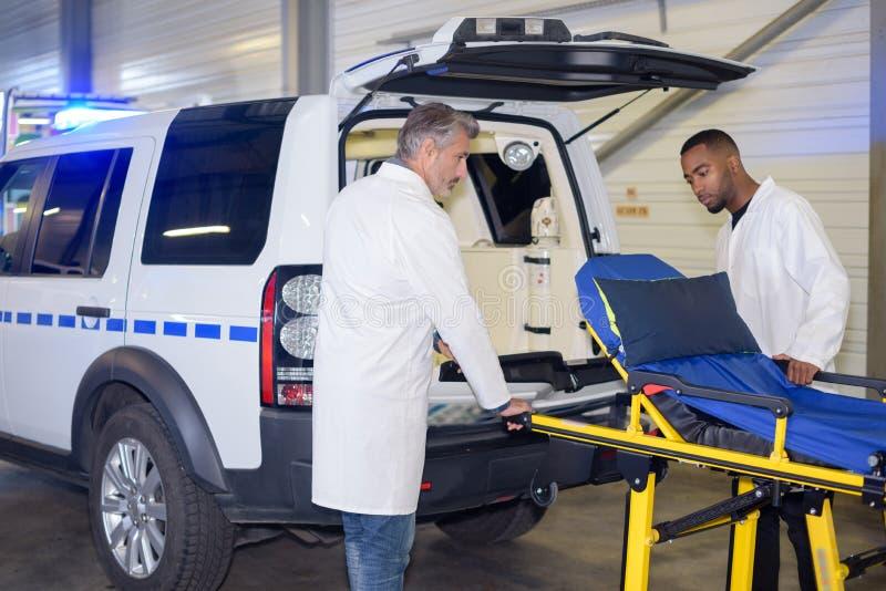 Paramédicos que rodam a maca para a ambulância imagens de stock royalty free