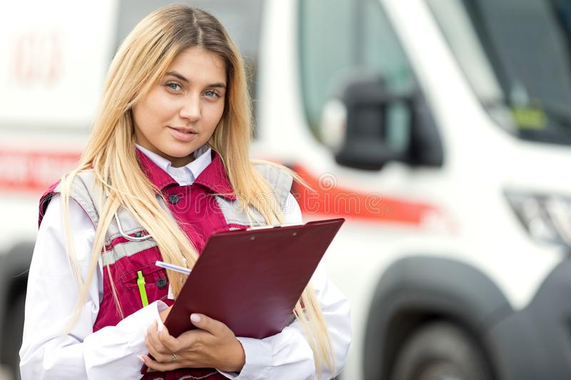 Paramedic with clipboard at emergency car background royalty free stock images