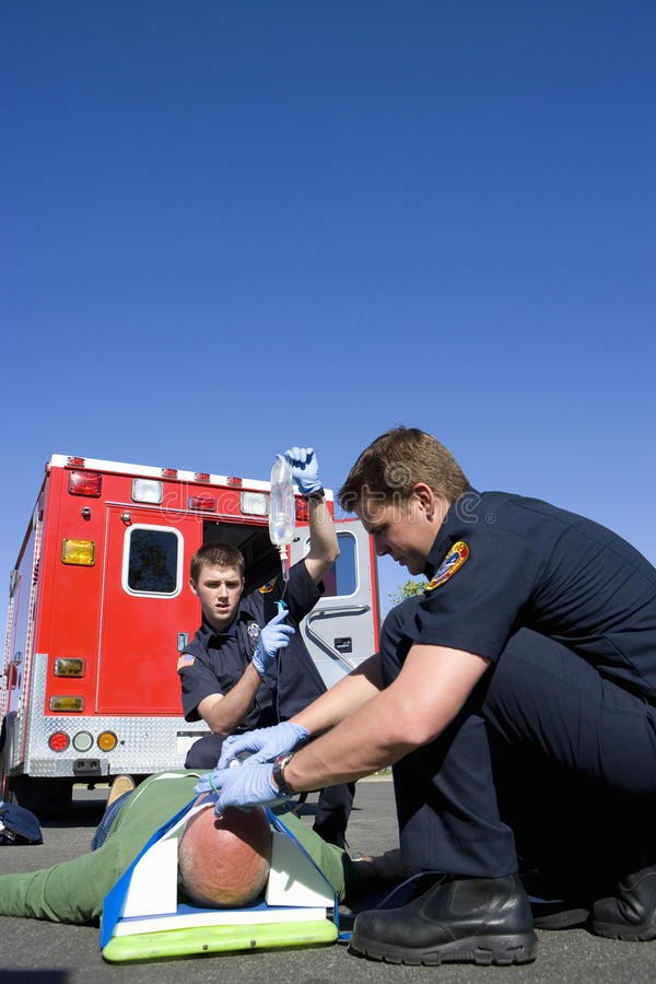 Paramedic and colleague helping man on stretcher by ambulance, low angle view stock photography