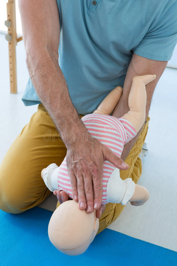 Paramedic demonstrating resuscitation on a infant dummy royalty free stock photo