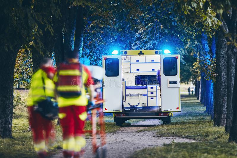 Team of Emergency medical service. Paramedic and doctor pushing stretcher with patient to emergency ambulance. Themes teamwork, rescue and hope royalty free stock photography
