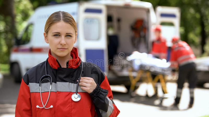 Paramedic posing for camera, ambulance crew transporting patient on background. Stock photo stock photo