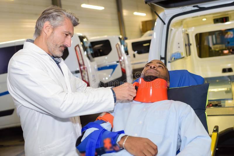 Paramedic securing neck brace to patient. Neck stock image