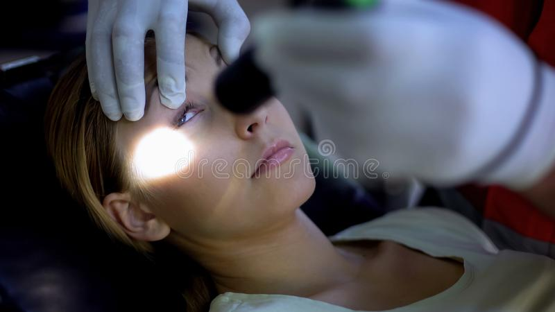 Paramedic shining light into patient eyes, testing pupil reflexes, first aid. Stock photo stock image