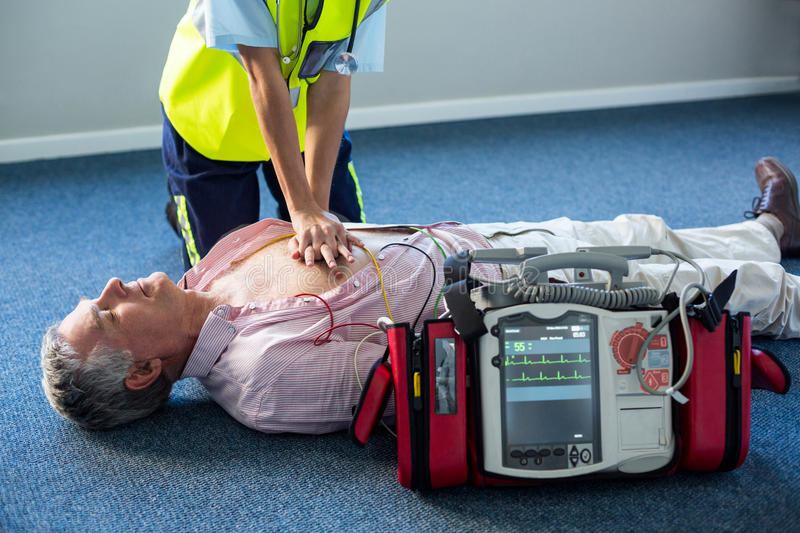 Paramedic using an external defibrillator during cardiopulmonary resuscitation. In hospital royalty free stock images