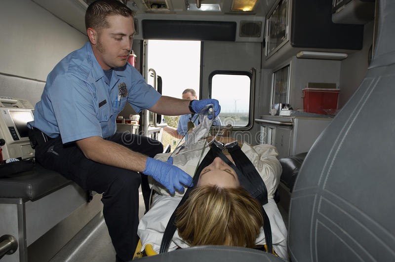 Paramedic With Victim In Ambulance stock image