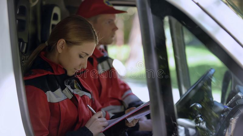 Paramedic writing report in ambulance, professionals on duty, emergency services. Stock photo stock photos
