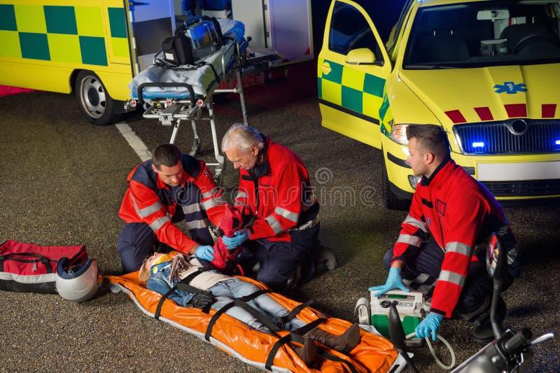 Paramedici che aiutano il driver della motocicletta sulla barella immagini stock libere da diritti