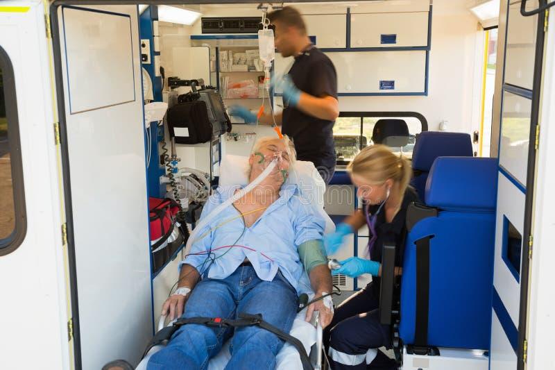 Paramedici che curano uomo incosciente in ambulanza immagini stock