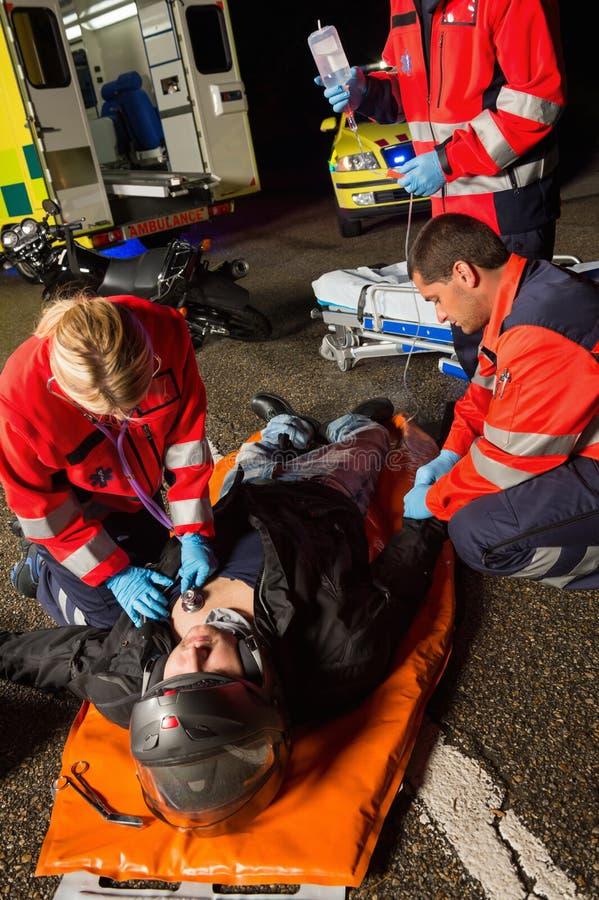 Paramedici die de verwonde bestuurder van de motorfietsmens onderzoeken stock foto
