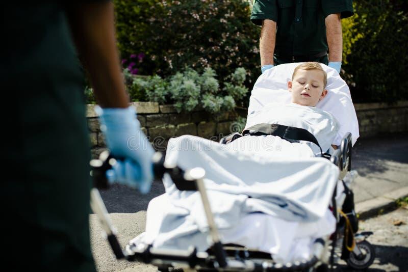 Paramedici die een jonge patiënt op een brancard verplaatsen naar een ziekenwagen stock afbeeldingen