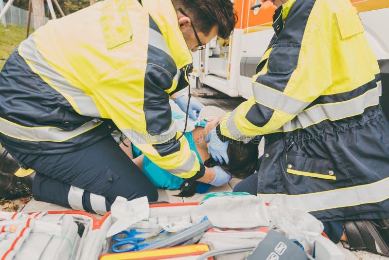 Paramedici die eerste hulp uitvoeren bij ziekenwagen royalty-vrije stock foto's
