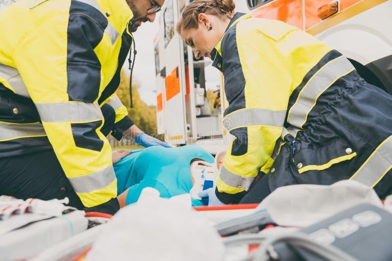 Paramedici die eerste hulp uitvoeren bij ziekenwagen royalty-vrije stock afbeeldingen