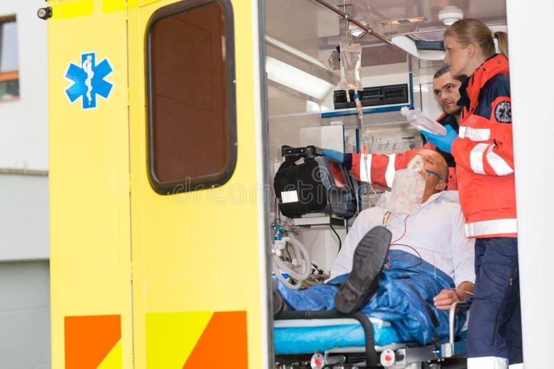 Paramedici die IV druppelpatiënt in ziekenwagen controleren stock foto