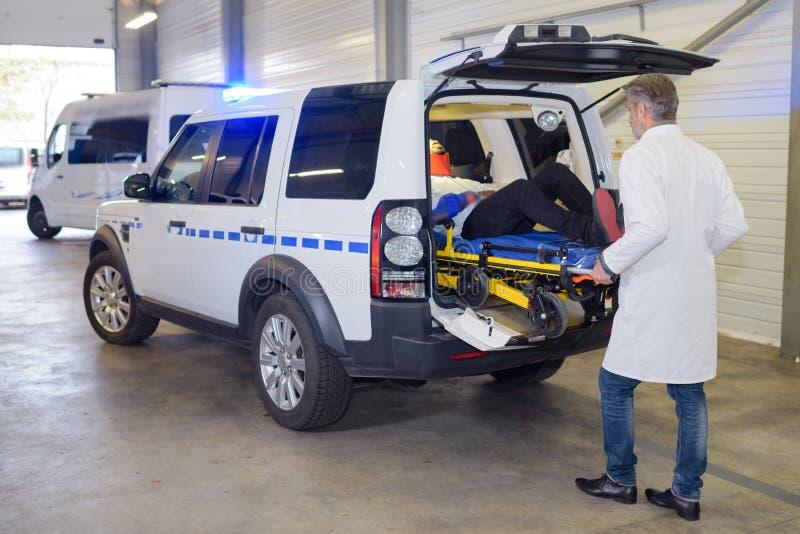 Paramedici die patiënt van ziekenwagen ontladen royalty-vrije stock fotografie