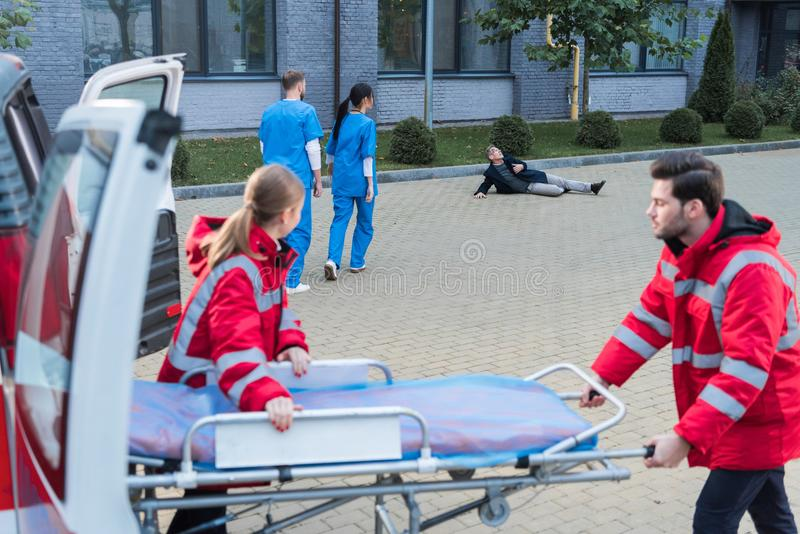 paramedici die te helpen ziekenwagenbrancard nemen royalty-vrije stock foto's