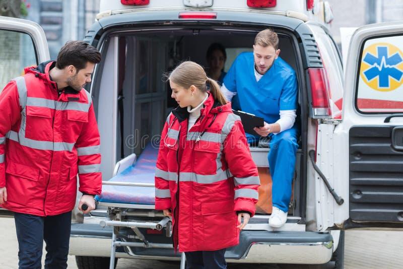 paramedici die uit ziekenwagenbrancard bewegen royalty-vrije stock foto's