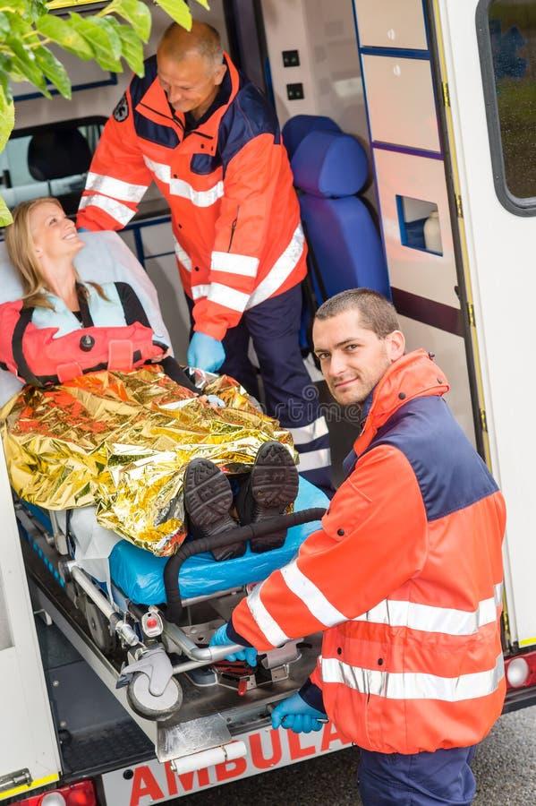 Paramedici die vrouw op brancard in ziekenwagen helpen royalty-vrije stock foto's