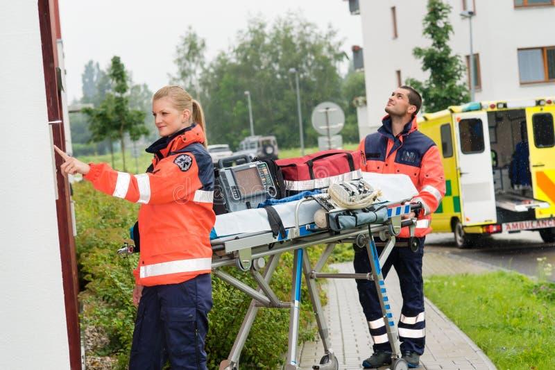 Paramedici met medische apparatuur bellende deurbel stock fotografie