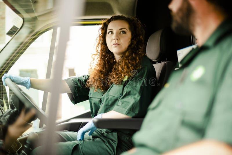Paramedicinsk kvinna som kör en ambulans arkivbilder