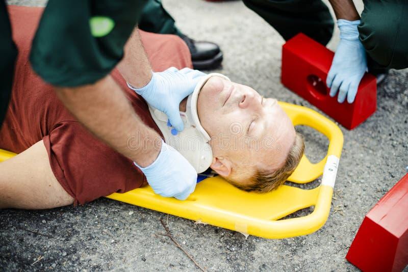 Paramedicinskt lag som förlägger en cervikal krage till en sårad man royaltyfri fotografi