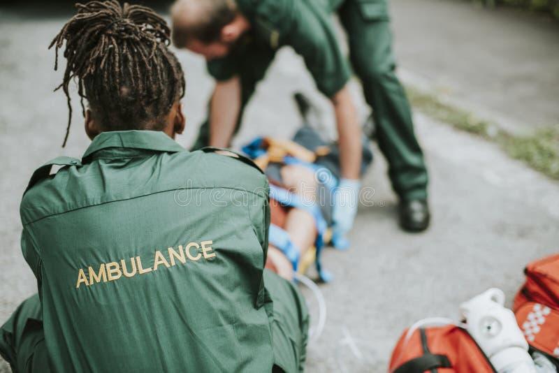 Paramedicinskt lag som räddar en sårad patient arkivbild