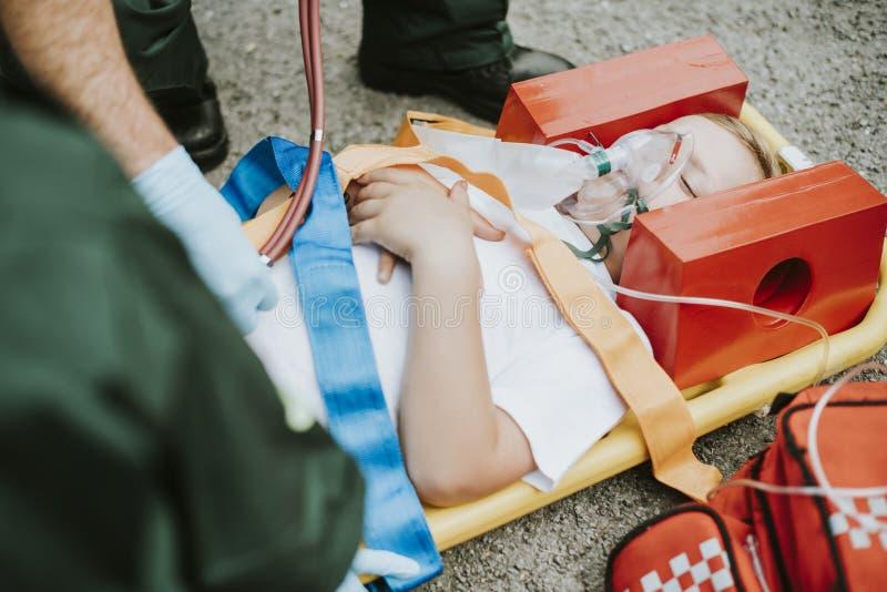 Paramedicinskt lag som räddar en ung kritisk patient royaltyfria bilder