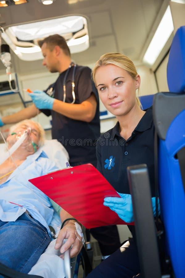 Paramedico che aiuta paziente danneggiato in ambulanza fotografia stock libera da diritti