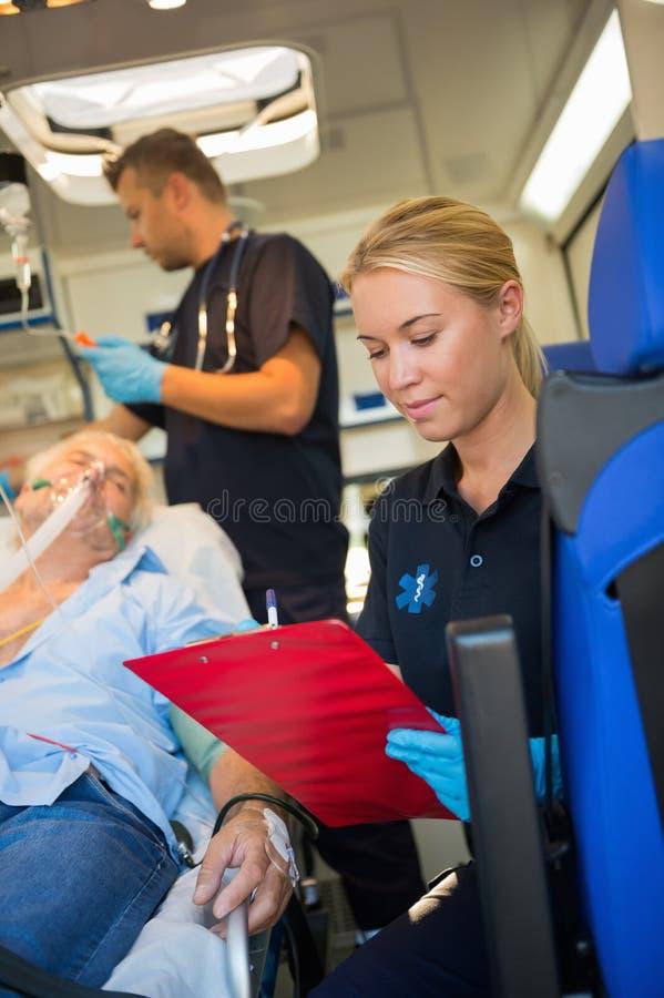 Paramedico che assiste paziente danneggiato in ambulanza fotografie stock libere da diritti