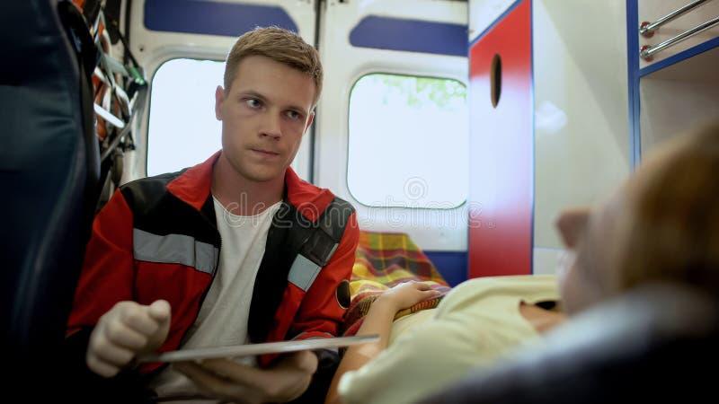 Paramedico che fa le domande pazienti e che compila forma medica in ambulanza fotografia stock