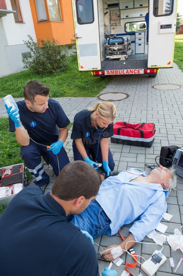 Paramedics που θεραπεύει το τραυματισμένο άτομο στην οδό στοκ εικόνα