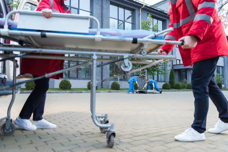 Paramedics moving ambulance stretcher to. Injured man royalty free stock images