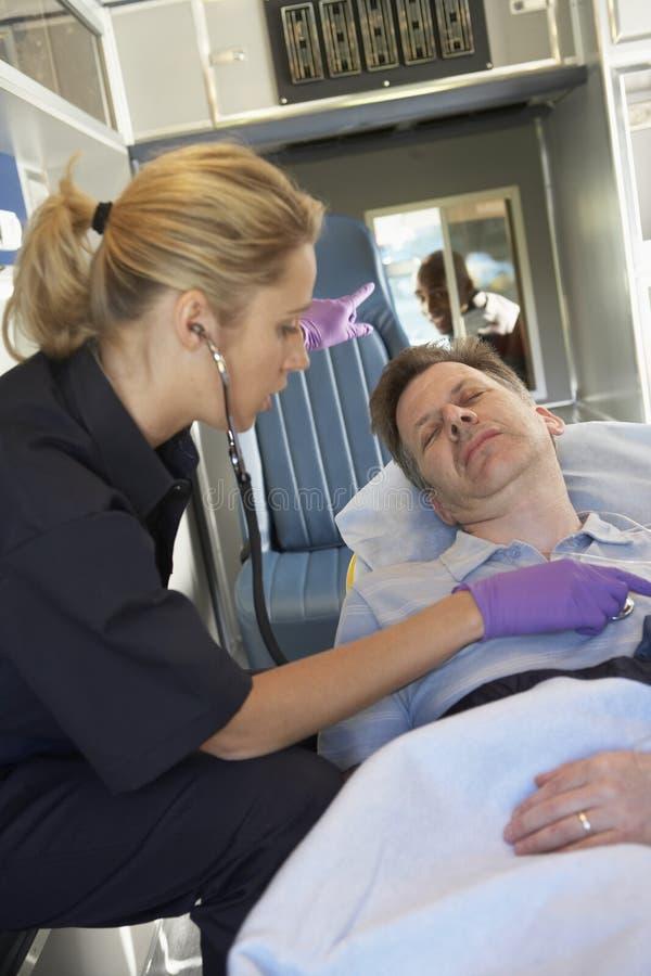 Paramedicus die bij patiënt in ziekenwagen aanwezig is royalty-vrije stock afbeeldingen