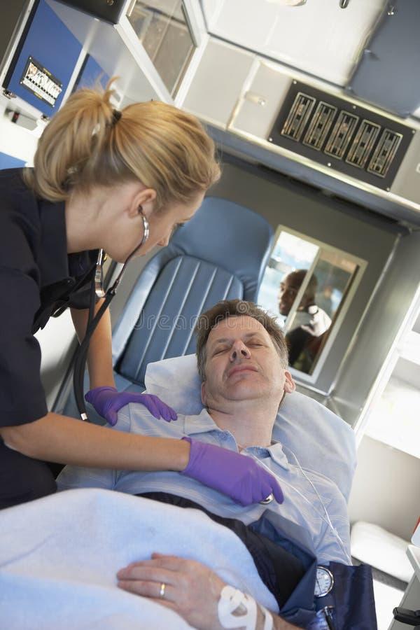 Paramedicus die bij patiënt in ziekenwagen aanwezig is stock foto's