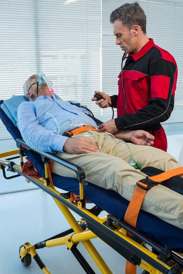 Paramedicus die bloeddruk van patiënt controleren stock fotografie