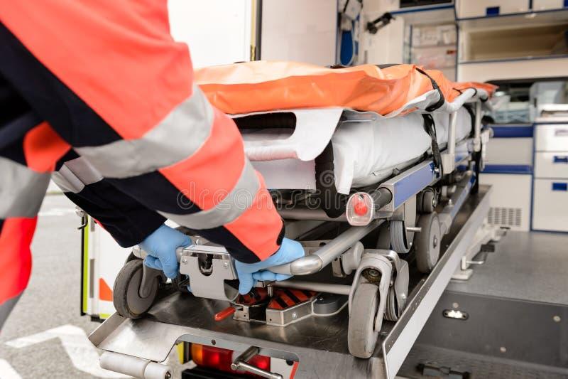 Paramedicus die gurney van ziekenwagenauto terugtrekken royalty-vrije stock fotografie