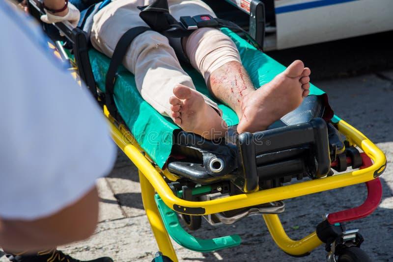 Paramedicus die hulp geven aan een gelaedeerde na ongeval op weg royalty-vrije stock afbeelding