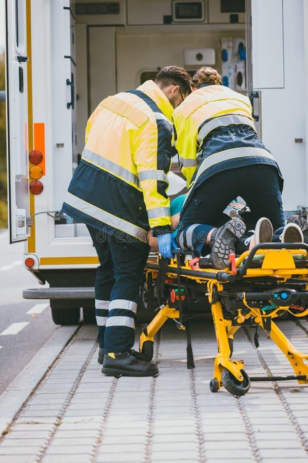 Paramedicus die op brancard voor het leven van verwonde vrouw vechten stock foto's