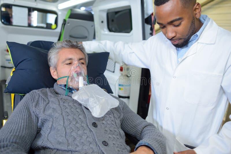 Paramedicus die patiënt voor vervoer voorbereiden aan het ziekenhuis royalty-vrije stock afbeelding