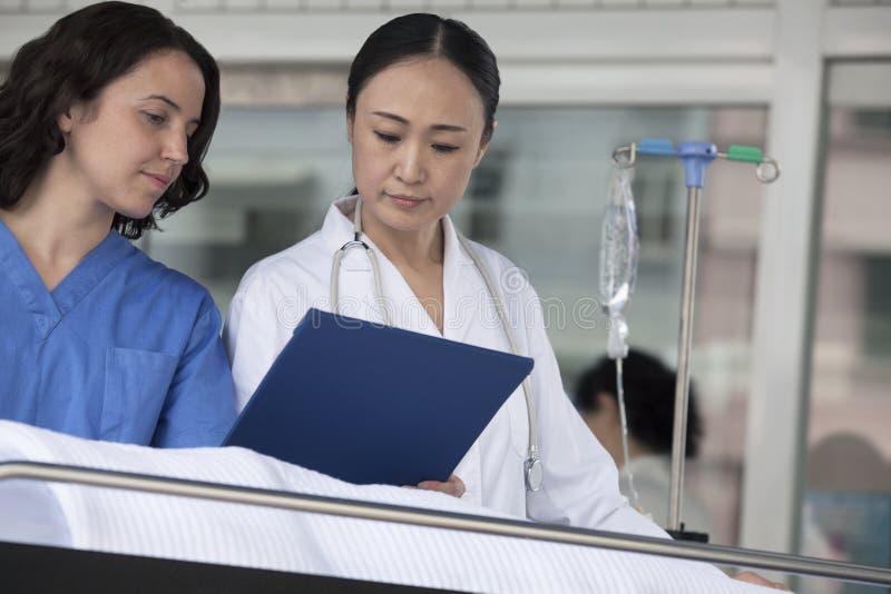 Paramedicus en arts die neer het medische dossier van patiënt op een brancard voor het ziekenhuis bekijken stock foto's