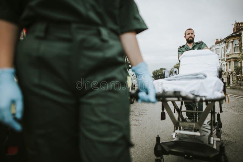 Paramedicusteam die een brancard op een straat rollen stock afbeelding