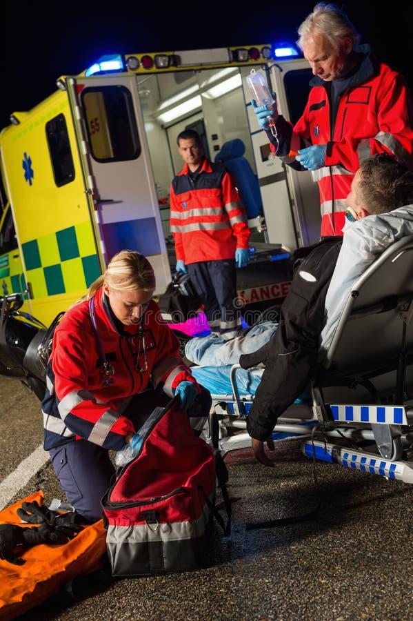 Paramedicusteam die verwonde motorbestuurder bijstaan royalty-vrije stock afbeeldingen