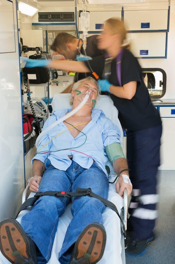 Paramedisch team die patiënt op brancard behandelen royalty-vrije stock afbeeldingen