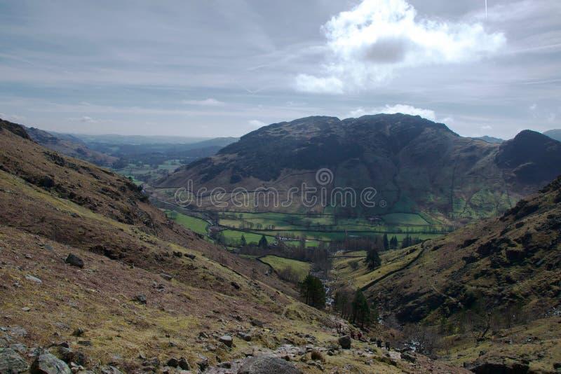 Paramera rocosa de la montaña de la hierba en primero plano; campos pastorales abajo en valle de la montaña imágenes de archivo libres de regalías