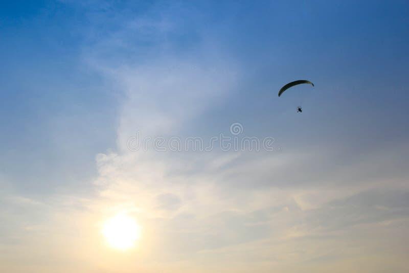Paramotor летания силуэта голубого неба стоковое фото