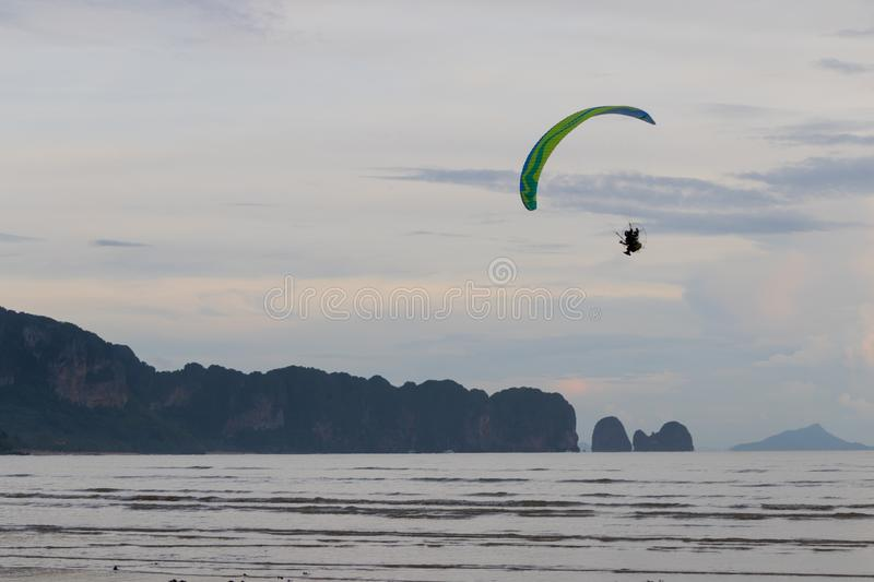 Paramotor is flying over the beach stock photo