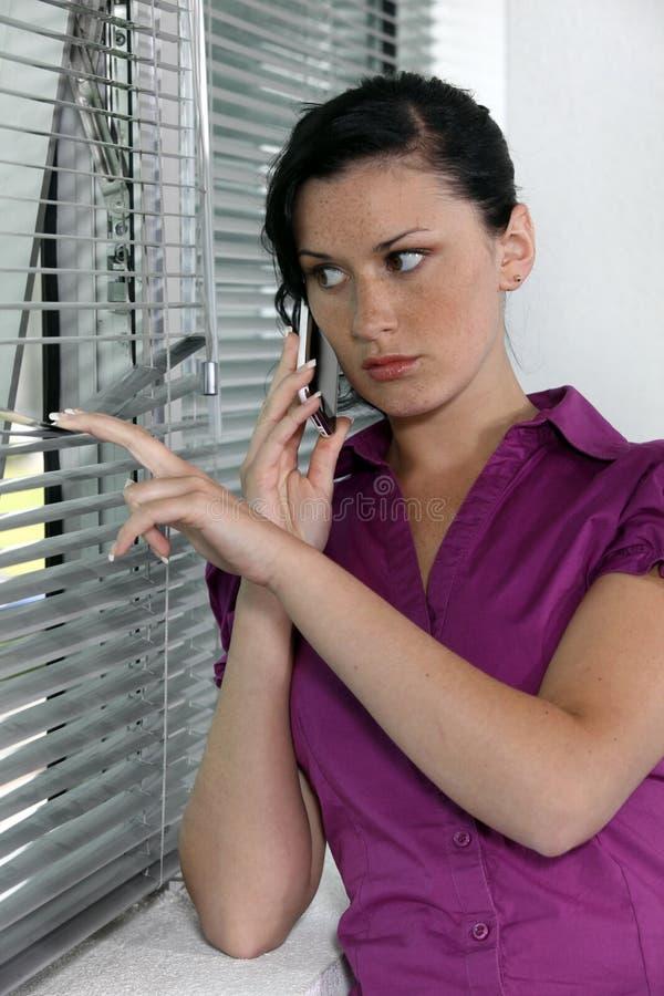 Paranoid woman looking through blinds stock photos