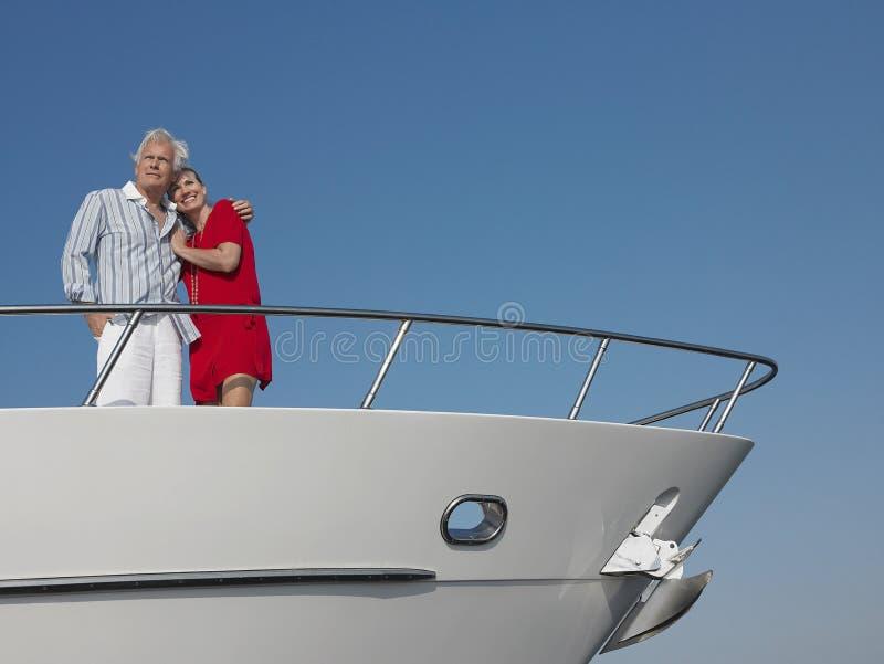 Paranseende med armen omkring på pilbåge av yachten arkivfoto