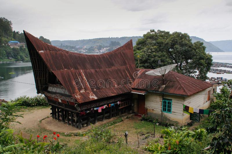 Unusual traditional houses with boat roofs of the Batak people on the island of Sumatra, Indonesia. The traditional architecture o. Parapat, Sumatra - January 30 stock image