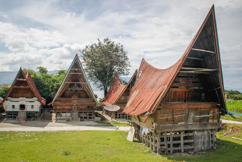Unusual traditional houses with boat roofs of the Batak people on the island of Sumatra, Indonesia. The traditional architecture o. Parapat, Sumatra - January 30 royalty free stock images